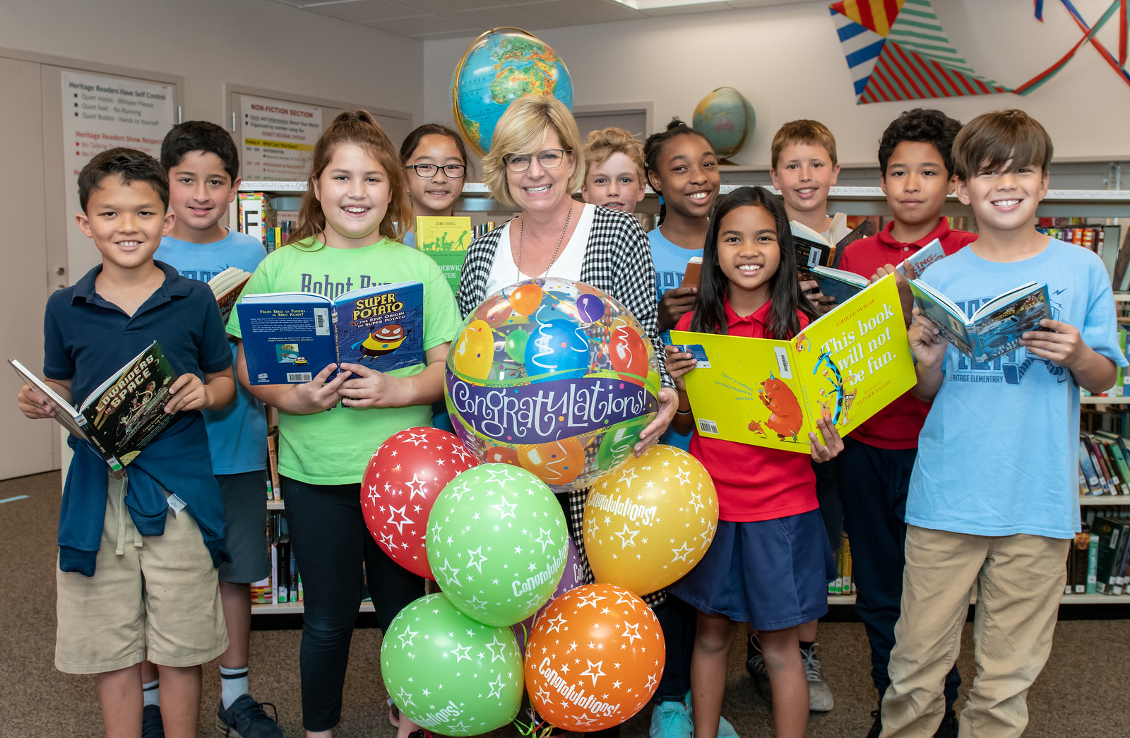 Honour Del Crognale holding balloons surrounded by students in the school library