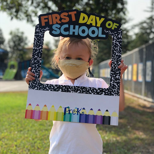 Student holding First Day of School sign wearing a mask.