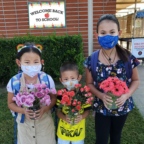 Three students wearing masks and holding flowers