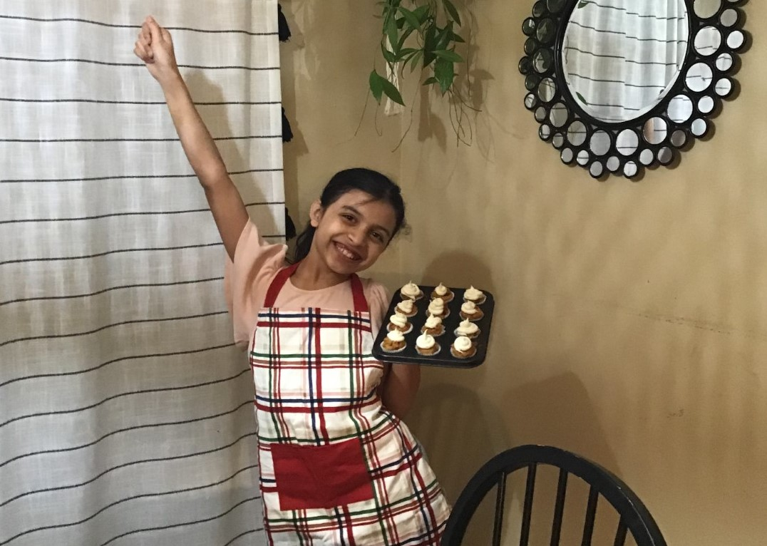 Laila Dorado wearing an apron, smiling and holding a tray of cupcakes.