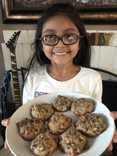 Brianna Tinoco smiling holding a plate full of freshly baked cookies