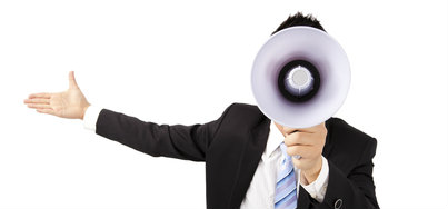 Man in a suit making an announcement into a megaphone