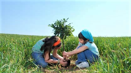 Arbor Day - Photo of two kids in field with sapling