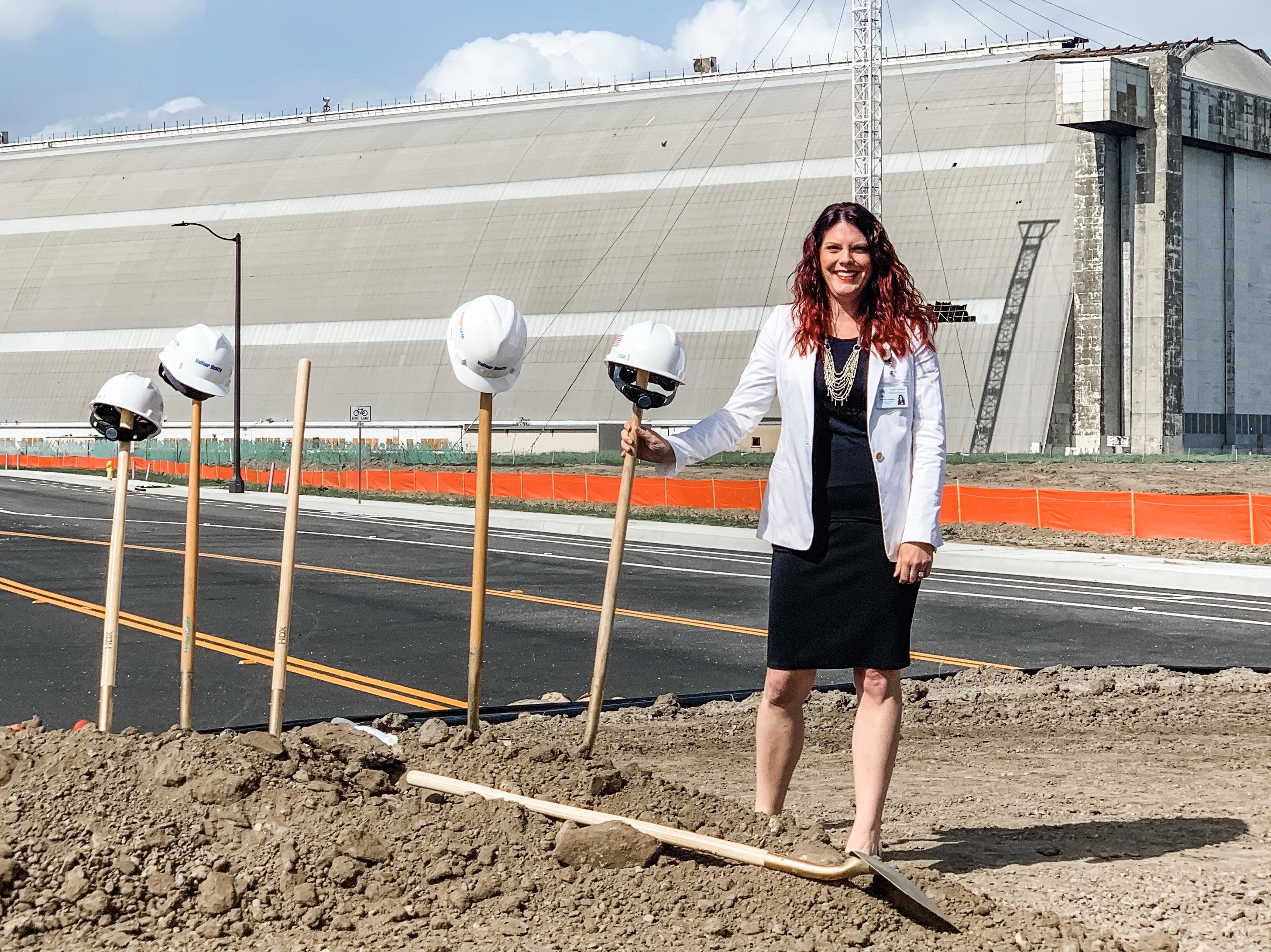 Jennifer Harrison holding shovel with blimp hangar in the background at the Legacy School groundbreaking
