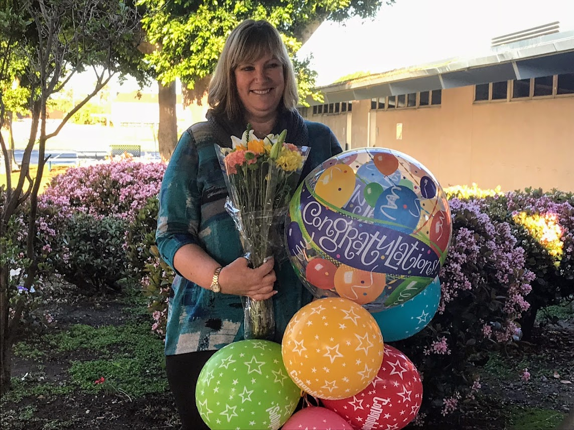 Photo of Patty Ellis with flowers and balloons