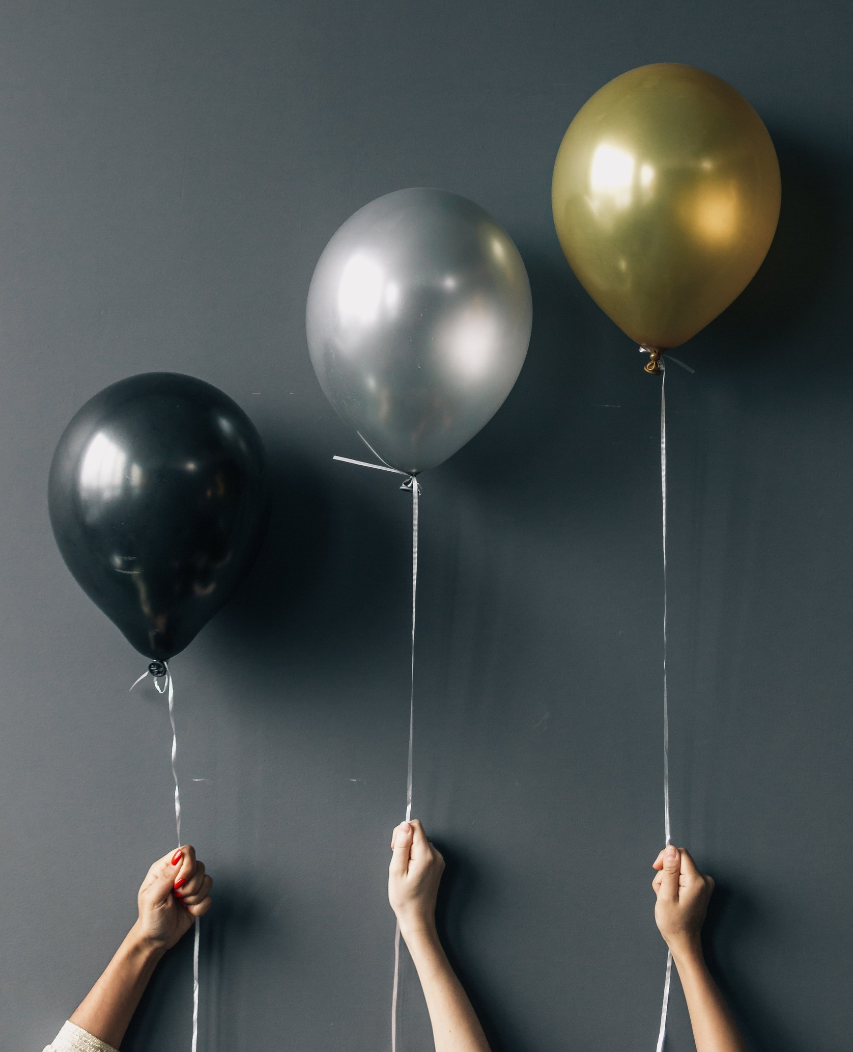 three balloons held against a wall