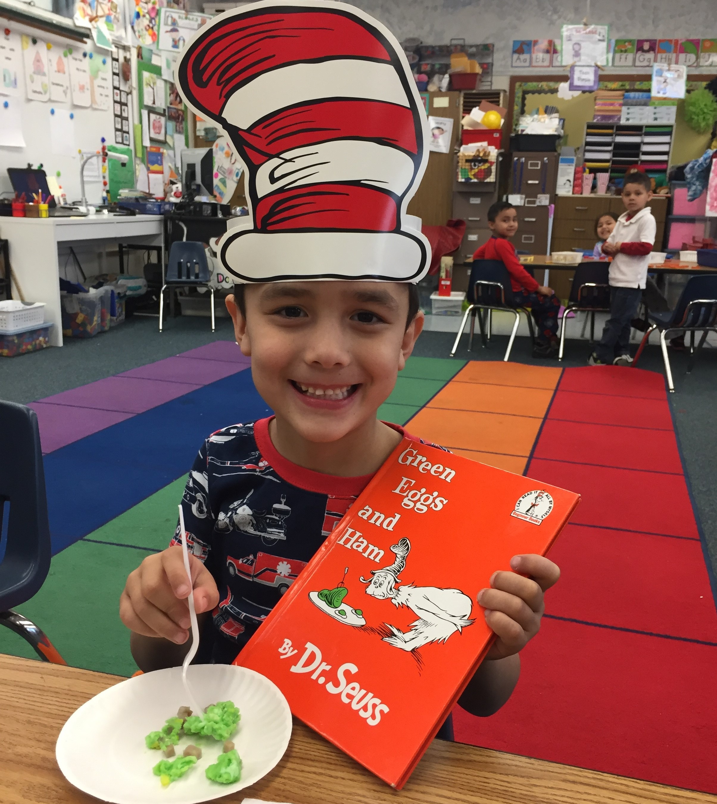 Photo of student with Dr. Seuss book, hat, and green eggs and ham