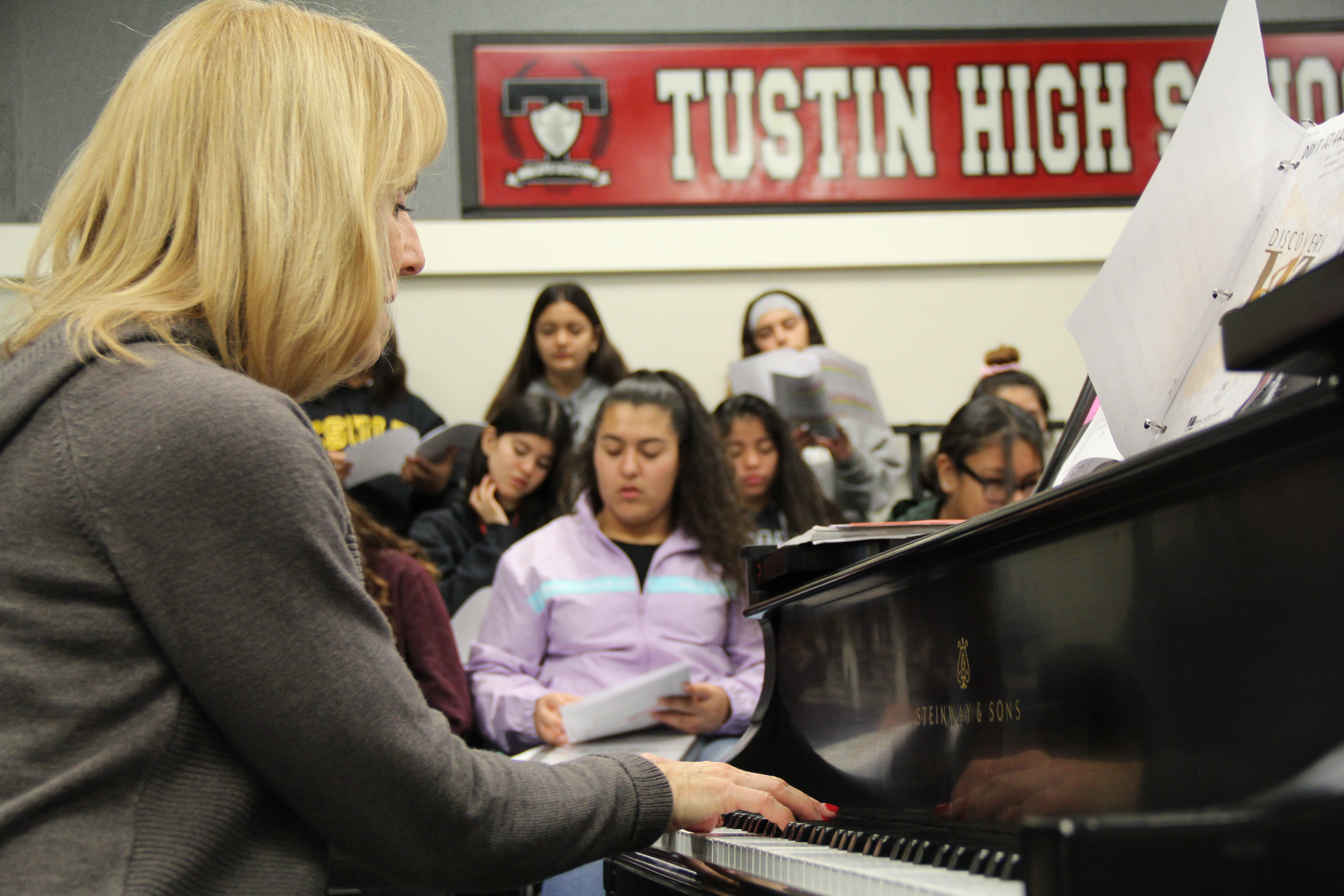 Ms Snider leading choir practice from her piano