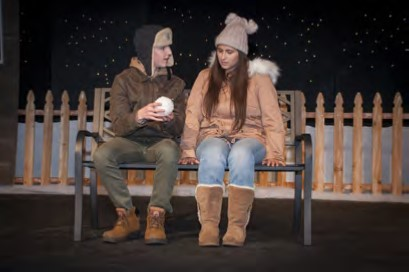 Male and Female on stage sitting on a bench in Winter Play 2018