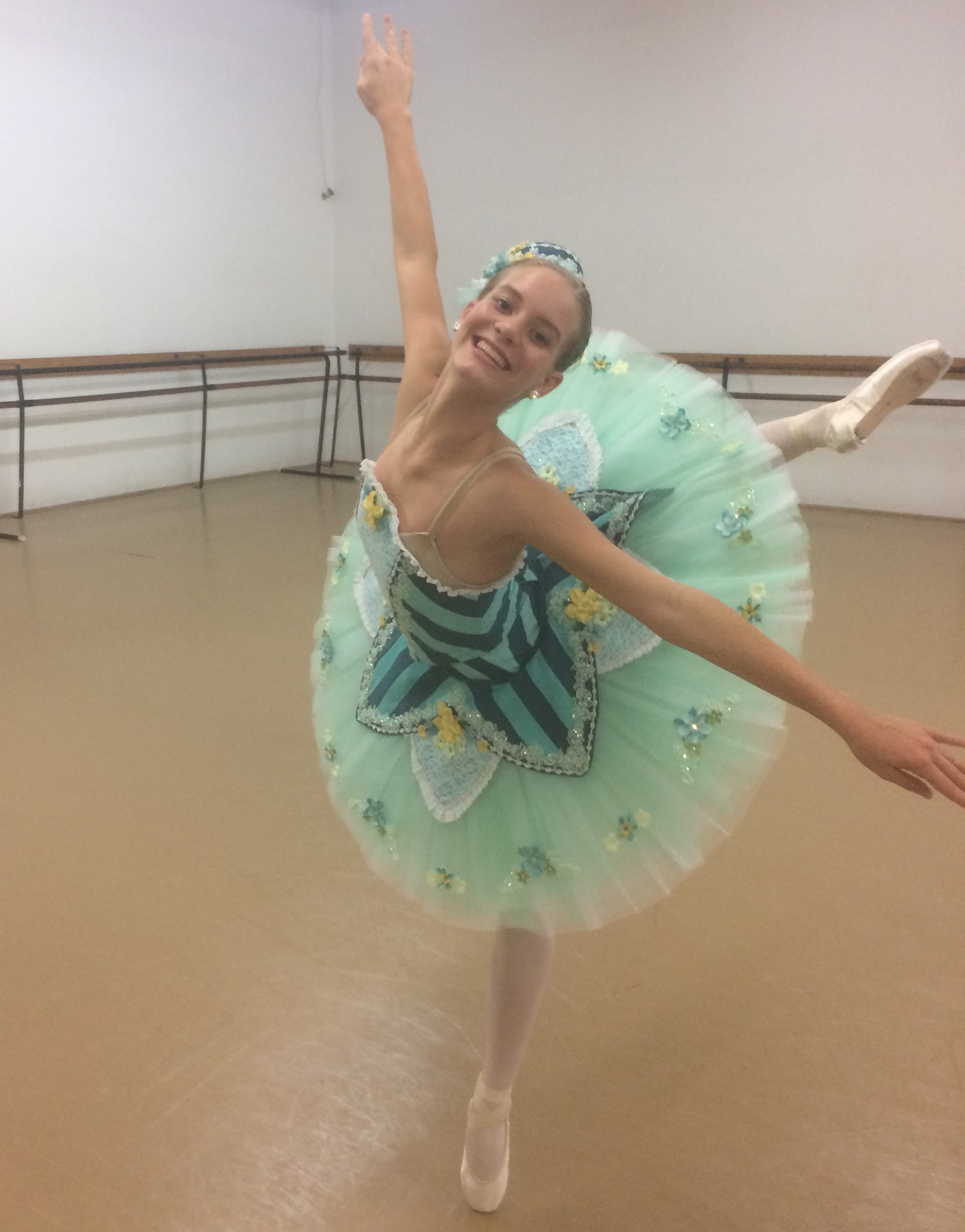 Maia McBride posing in arabesque wearing a green tutu